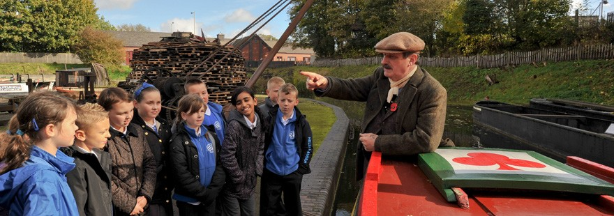 A man on a barge talking to school children at black country living museum