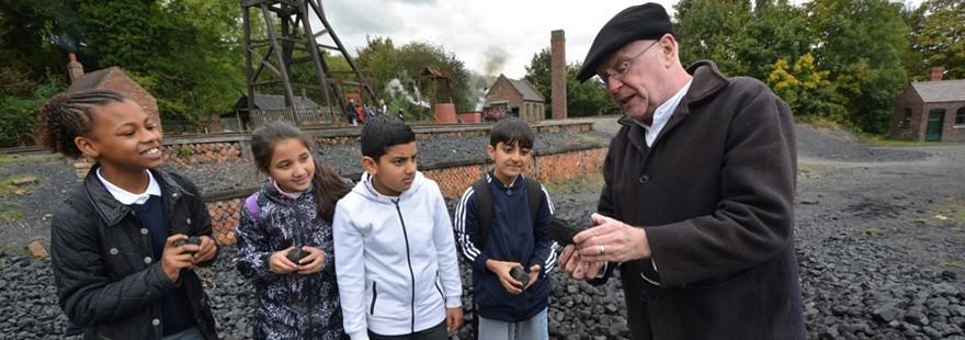 A blacksmith talking to school children